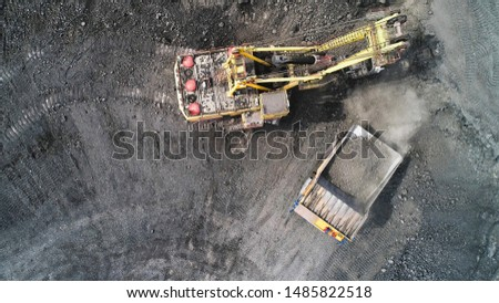 Cable excavator loads overburden from the body of a mining truck. Excavation of gangue from the face of a quarry. #1485822518