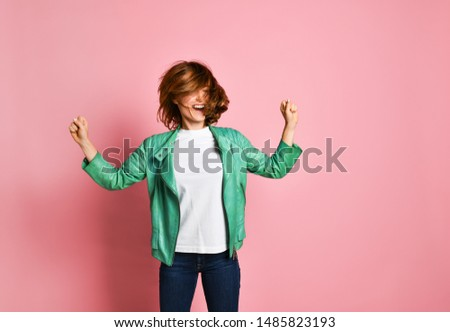 young woman wearing jeans and a jacket is shaking her head with her hair. The concept of joy, happiness, joy, fun #1485823193