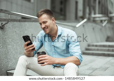 young handsome office worker holding smartphone and drinking coffee during lunch break sitting on the stairs in the street #1485849527