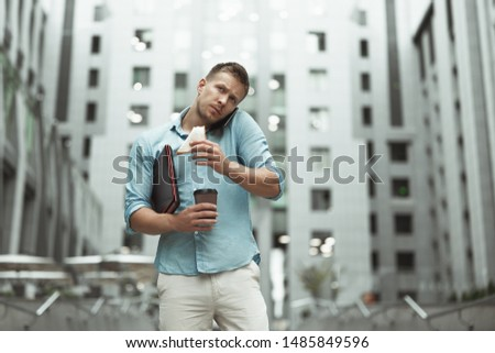 young handsome office worker talking on phone holding laptop and cup of coffee eating sandwich walking down the street near business center #1485849596