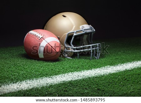 A low angle view of a gold football helmet with a football on a grass field with stripe and dark background #1485893795