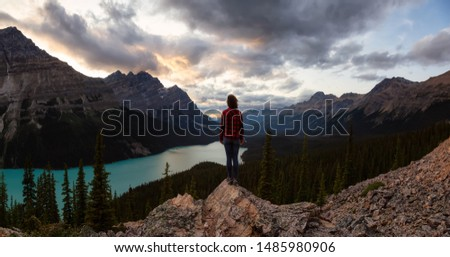 Adventurous girl standing on the edge of a cliff overlooking the beautiful Canadian Rockies and Peyto Lake during a vibrant summer sunset. Taken in Banff National Park, Alberta, Canada. #1485980906