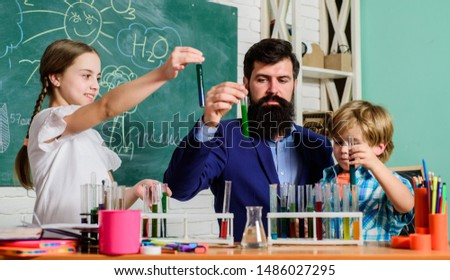 Kids can grow in area of club such as science. School club education. Teacher and pupils test tubes in classroom. Chemistry themed club. Discover and explore properties of substances together. #1486027295