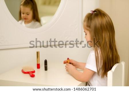A little girl near the mirror paints lipstick lips #1486062701
