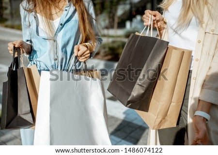Women holding shopping bags outdoors while shopping, close-up view on the empty paper bags with copy space #1486074122