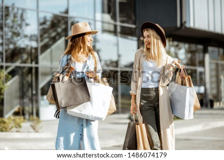 Two happy girlfriends walking with shopping bags in front of the shopping mall, feeling satisfied with new purchases #1486074179