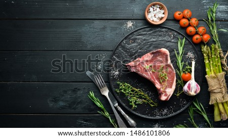 Raw T-bone steak on a wooden table. Top view. Free space for text. #1486101806