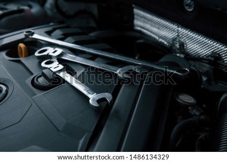Three wrenches. Repair tools lying down on the engine of automobile under the hood. #1486134329