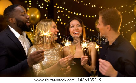 Happy group of friends holding bengal lights and wine glasses, New Year greeting #1486135319