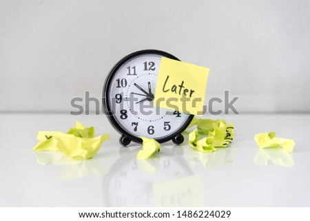 Procrastination delay and urgency concept with word later on sticky paper over white alarm clock and crumpled paper ball, bad time management. Royalty-Free Stock Photo #1486224029