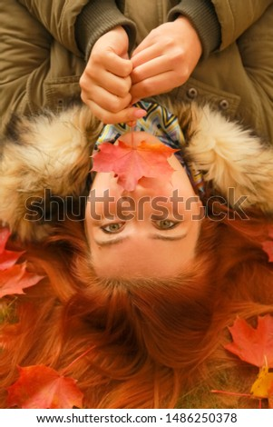 young pretty plus size caucasian woman lies on the ground in autumn park top view #1486250378
