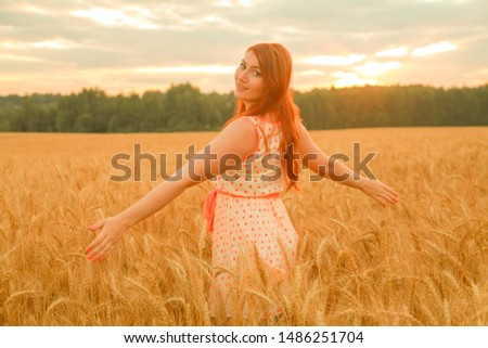 girl in dress walking in golden ripe wheat field at sunset #1486251704