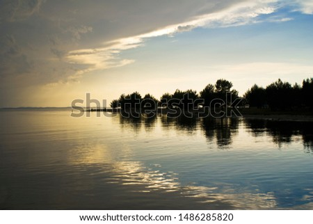 sunset on the lake and silhouette of the forest #1486285820