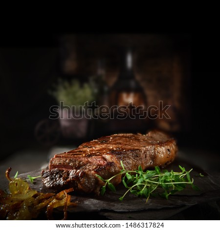 Succulent Farmhouse Rustic Rump Steak with thyme garnish shot against a dark background with wood burner. The perfect image for your bistro or restaurant menu cover art. Copy space. #1486317824