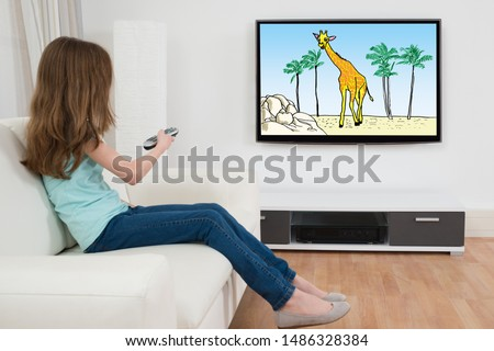 Side View Of Girl Sitting On Sofa Watching Cartoon On Television