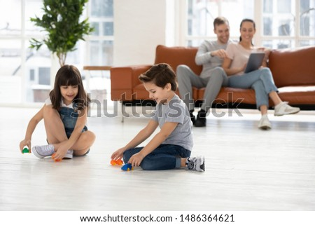 Happy family leisure at home concept, young couple parents relaxing using device on sofa couch in comfort living room while small kids children son daughter enjoy activity play toy cars on warm floor #1486364621