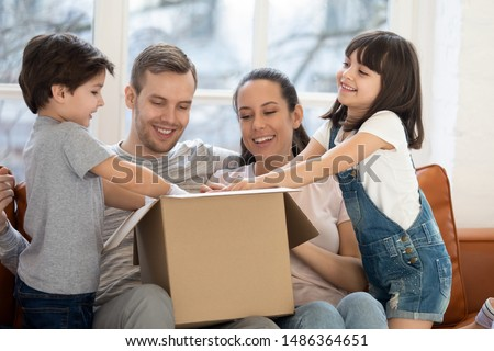 Happy family with kids customers renters open cardboard box receive parcel unpack after relocation, cute children helping parents unbox package at home, post shipping delivery and moving day concept #1486364651