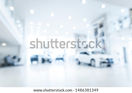 Blurred abstract dealership store, with defocused cars, clients and staff with  soft lightning #1486381349