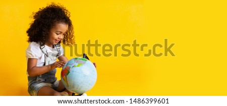Early education. Little girl pointing to world globe, yellow background, copy space Royalty-Free Stock Photo #1486399601