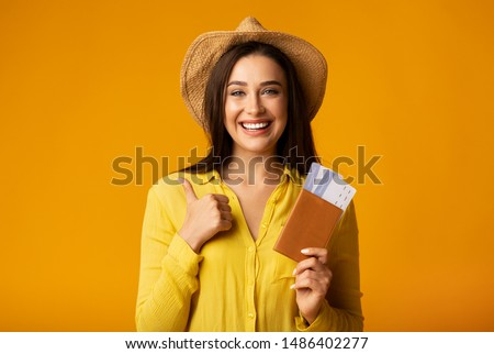 Cheap Flight Deals. Girl Holding Tickets And Passport Gesturing Thumbs-Up On Yellow Studio Background. Copy Space