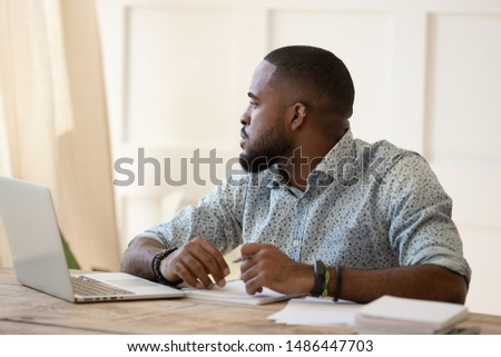 Unfocused bored tired black young man feeling bored during remote work or online courses study, having lack of motivation or energy. Overworked black guy feeling lazy, having monotonous job. #1486447703