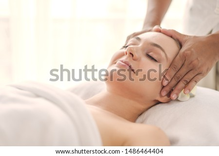 Beautiful young woman relaxing with hand massage at beauty spa. Face massage. Closed up of young beautiful woman getting spa massage treatment at beauty spa salon. #1486464404