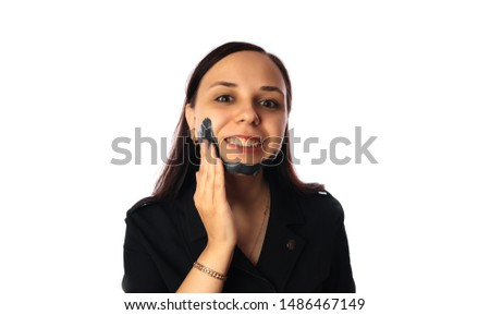 A young woman inflicts a black mask on the face isolated on white background.The concept of healthy lifestyle, beauty, body care. #1486467149