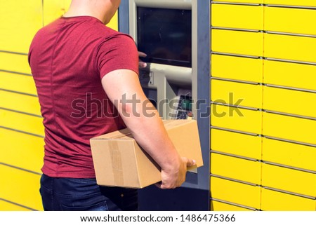 Man using automated self-service post terminal machine or locker to depisit a parcel for storage #1486475366