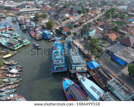 skewed harbor cities and vessels, fishing vessels in Indonesia and Asia. The mouth of the river as a berth view from above with aerial drone camera #1486499558
