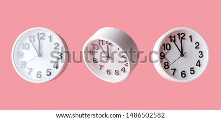 White clock on bright pink background. Minimal time concept.
