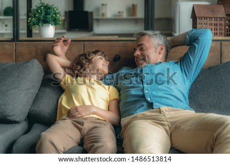 Cheerful mature father spending day together with little son and sitting on couch #1486513814