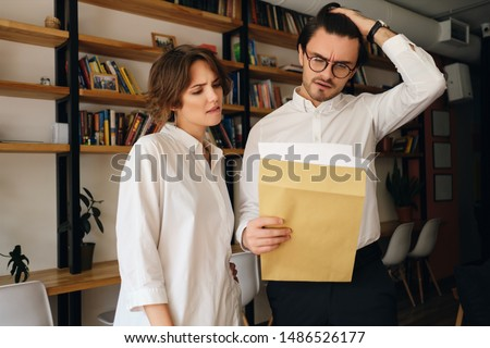 Young disappointed business colleagues thoughtfully reading envelope letter working together in modern office #1486526177