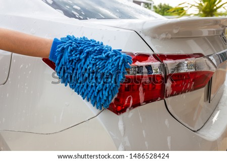 Woman hand with blue microfiber fabric washing taillight modern car or cleaning automobile. Car wash concept #1486528424