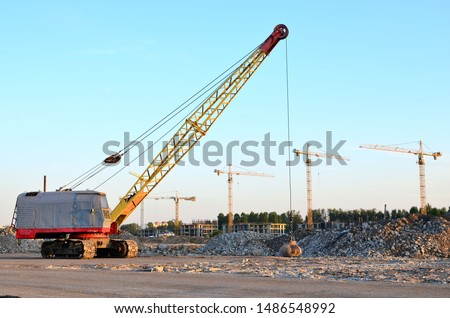 Large crawler crane or dragline excavator with a heavy metal wrecking ball on a steel cable. Wrecking balls at construction sites. Dismantling and demolition of buildings and structures - Image Royalty-Free Stock Photo #1486548992