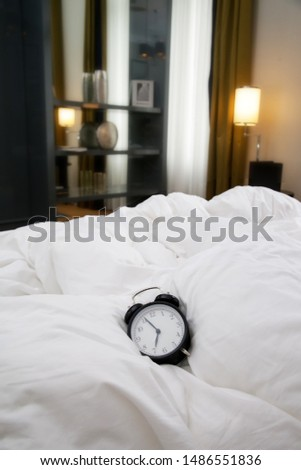 Classic black alarm clock on the white wrinkled bed sheets	 #1486551836