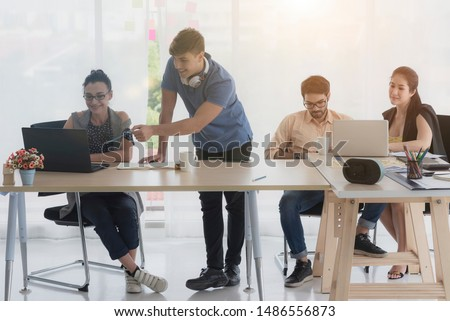 business team working on laptop to check the results of their wo #1486556873