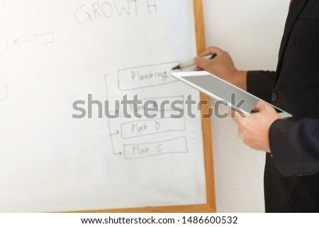 Businessmen holding a tablet are describing a business plan (Plan A, Plan B, Plan C). #1486600532