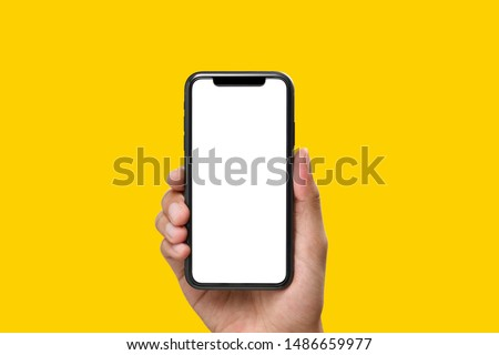 Hand holding the black smartphone with blank screen on yellow colour background Royalty-Free Stock Photo #1486659977