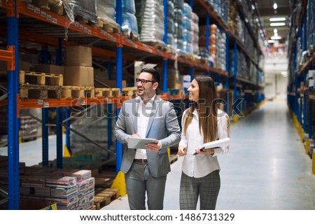 Two successful business people walking through large warehouse center. Manager smiling and looking shelves full with packages and products. Warehouse workers talking about logistics and distribution. #1486731329