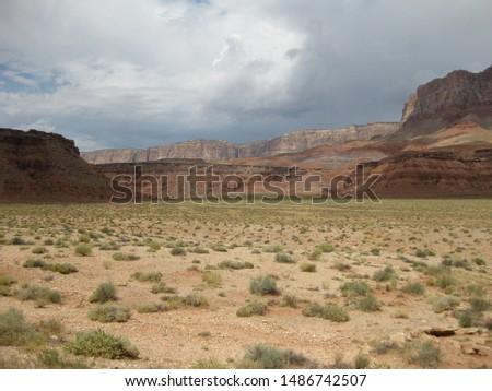 Storm brewing over the high desert in the southwestern United States. Red rock mesas with colorful strata.