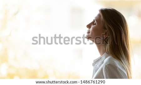 Calm happy business woman breathing fresh air standing at window, mindful lady take deep breath meditate feel no stress free relief enjoy wellbeing practice yoga exercise at home office, side view Royalty-Free Stock Photo #1486761290