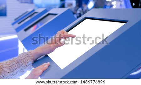 Woman hand using white blank interactive touchscreen display of electronic multimedia in dark room - scrolling and touching - close up view. Mock up, copyspace, template and technology concept #1486776896