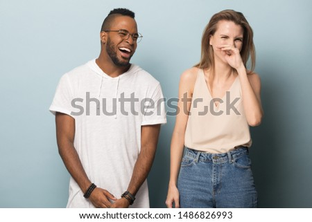 Happy multiethnic young people stand isolated on blue studio background laugh at funny joke together, excited african American man and Caucasian woman in casual wear have fun smile and giggle Royalty-Free Stock Photo #1486826993