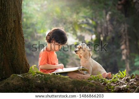 Asian boy and dog. Kid read book. Child and puppy under tree. American Cocker Spaniel home pet. Domestic animal. School and education. Nature and park. Early learning. Summer outdoor. Best friends.  #1486866203