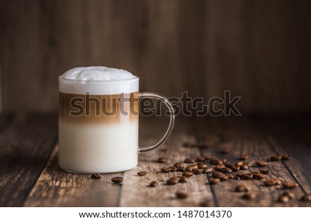 Cafe latte macchiato layered coffee in a see through glass coffee cup. The cup is on a wooden background with coffee beans on the table next to the cup. #1487014370