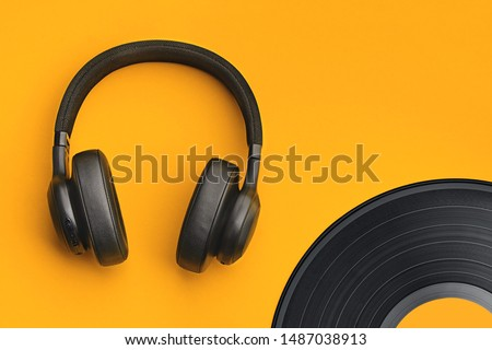 Black wireless headphones with vinyl record on a colored background. Music concept with copyspace. Headphones on orange background isolated #1487038913