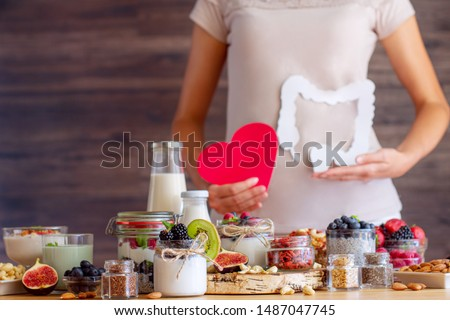 Female is holding figures of heart and intestines. Summer breakfast with organic yogurts fruits, berries and nuts. Nutrition that promotes good digestion and functioning of gastrointestinal tract. Royalty-Free Stock Photo #1487047745