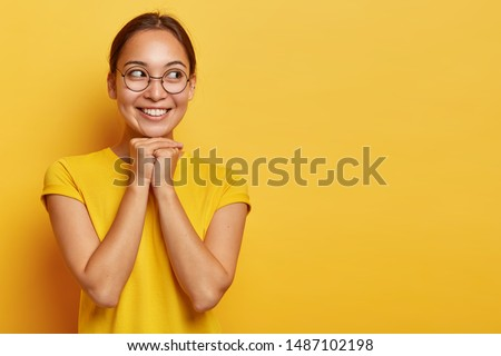 Happy eastern girl looks joyfully aside, holds hands under chin, being delighted and dreamy, focused aside, has dark hair, wears spectacles and t shirt, isolated on yellow studio wall with empty space #1487102198