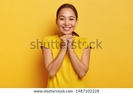 Photo of charismatic Asian female keeps hands together near chin, smiles gently, has cute expression, dark hair combed in pony tail, wears vivid yellow t shirt, entertained in awesome company #1487102228