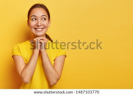 Joyous Eastern girl looks with dreamy hopeful expression on right copy space, keeps hands pressed together, imagines pleasant scene, has natural beauty, dark hair, pleasant appearance, poses indoor #1487103770